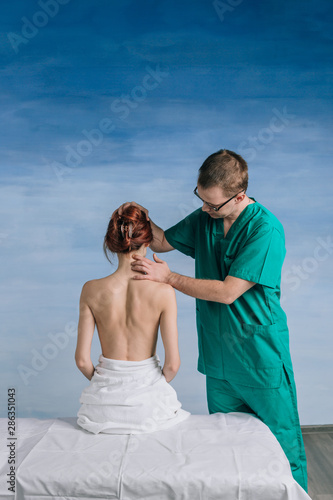 The male doctor examines the patient woman 27 years old on the blue background Wallpaper Mural