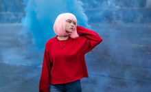 Stylish Ethnic Teenager Standing In Blue Smoke