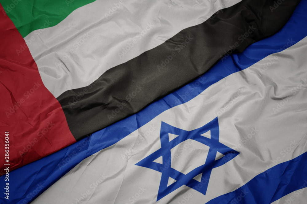 Fototapeta waving colorful flag of israel and national flag of united arab emirates.