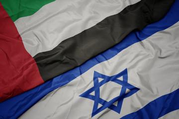 waving colorful flag of israel and national flag of united arab emirates.