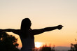 silhouette of womasilhouette of young woman with open arms raised in a sunsetn relaxing her arms at sunset