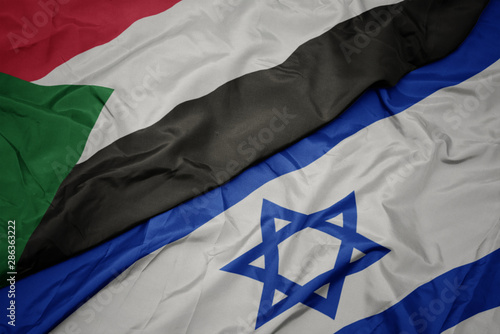 Stampa su Tela waving colorful flag of israel and national flag of sudan.