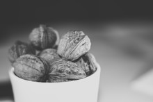 Black And White Photo Of White Bucket Full Of Nuts On Black Background