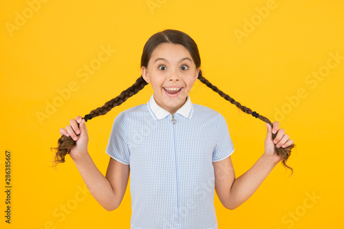 Cute braids. Tender schoolgirl on yellow background. Tidy hairstyle. Little girl with cute braids. Beautiful braids. Braided hairstyle concept. Girl with braided hair style. Hairdresser salon