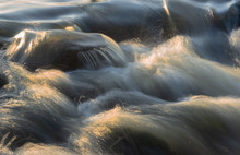 Long Exposure Of Water Floating Over Rocks In River, With Sunlight Giving The Water A Golden Color