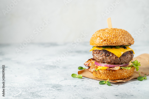 Fototapeta homemade delicious burger of beef, bacon, cheese, lettuce and tomatoes on a light concrete background. Fat unhealthy food close-up. With copy space obraz