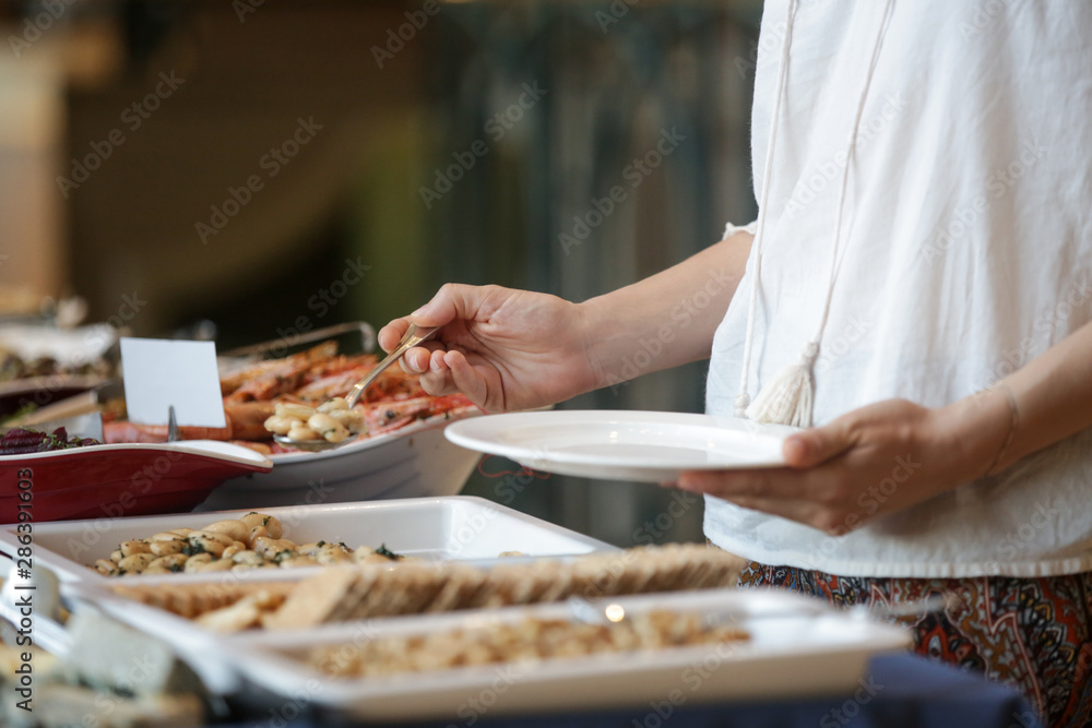 Fototapeta Woman taking food from a buffet line