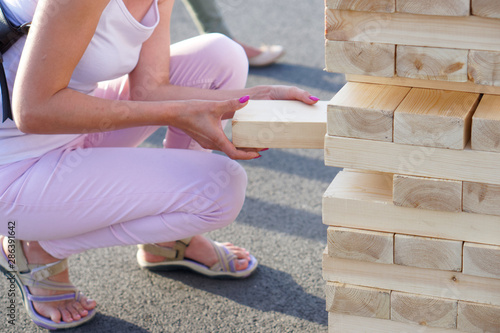 Fototapeta A girl in pink takes out one bar from the tower while playing a giant jenga. Outside obraz