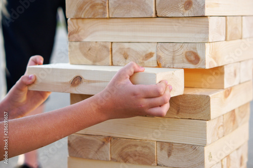 Fotografía A child takes out one bar from the tower while playing a giant jenga
