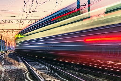 Passenger train moves fast at sunset time. Fototapeta