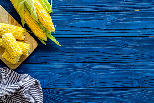 Fotografie, Obraz Corn on cobs on blue wooden background top view copyspace