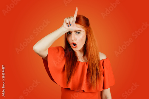 Fotografie, Obraz  woman giving loser sign on forehead looking at you disgust on face