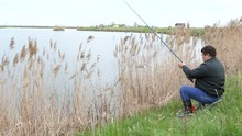 Young Asian Fisherman Sitting On A Shore Lake Casts A Fishing Rod Into The Lake.