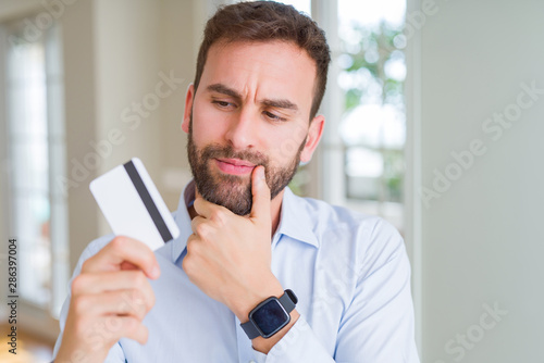 Photo sur Toile Les Textures Handsome business man holding credit card serious face thinking about question, very confused idea