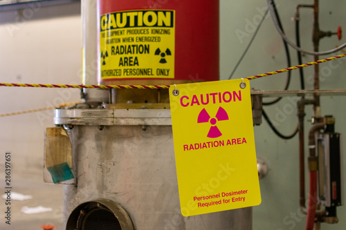 Obraz Ionizing radiation hazard symbol, radiation area and personnel dosimeter required text on yellow warning sign displayed on the equipment that produces ionizing radiation  - fototapety do salonu