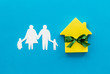 Buying a new house concept with house figure and family on blue background top view