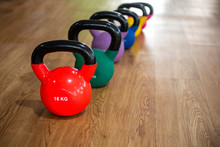Colorful Kettlebells In A Row On Wooden Floor In A Gym, Red, Green,purple,blue,yellow And Pink Color