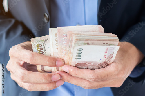 Photo Businessman hand holding Thai Baht banknote stack