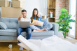 Young beautiful couple relaxing sitting on the sofa of new house using computer laptop pointing with finger to the camera and to you, hand sign, positive and confident gesture from the front