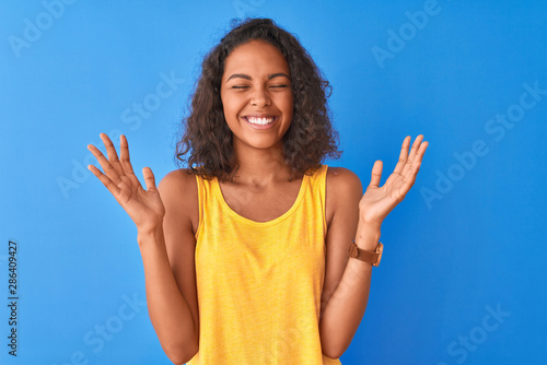 Vászonkép  Young brazilian woman wearing yellow t-shirt standing over isolated blue background celebrating mad and crazy for success with arms raised and closed eyes screaming excited