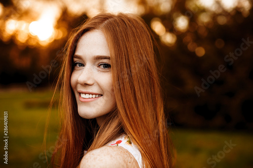 Close up portrait of a red hair woman girl with freckles looking at camera laughing over the shoulder against sunset outside Wallpaper Mural