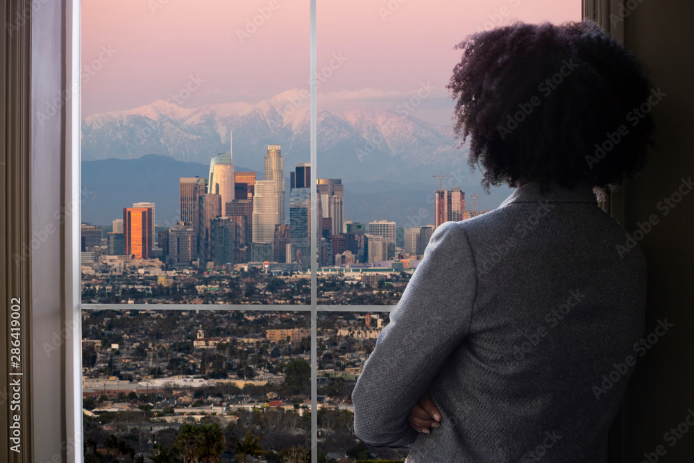 Fototapeta Black female business woman looking out the window of an office in Los Angeles.  She looks like a female architect thinking of urban development or a city mayor or governor planning zoning laws.