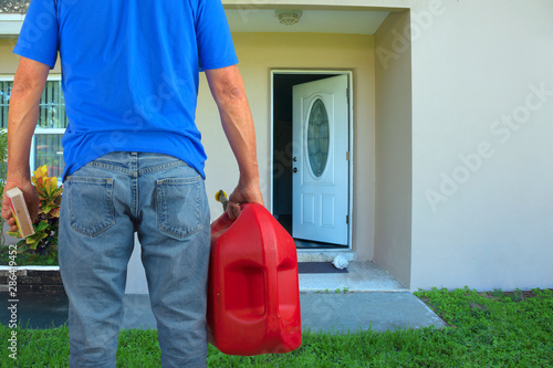 Arsonist man with red plastic gasoline can container and box of striking matches preparing to commit arson crime and maliciously and  intentionally burn down a house with an open front door Wallpaper Mural