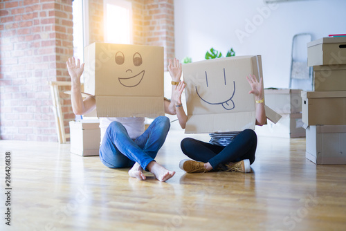 Foto auf Gartenposter Lineale Wachstum Couple wearing funny cardboard boxes with happy faces, moving to a new house, crazy and creative concept