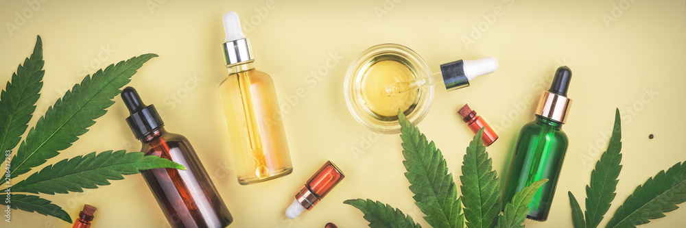 Fototapety, obrazy: Different glass bottles with CBD OIL, THC tincture and cannabis leaves on yellow background. Flat lay, minimalism. Cosmetics CBD oil.