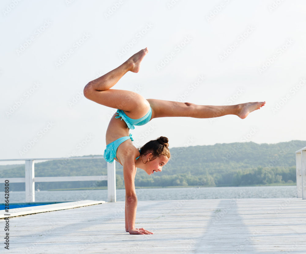 Fototapeta Gymnast little girl child doing acrobatic exercises outdoors on a beach