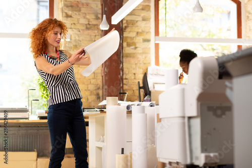 Fotomural  Worker of publishing office checking quality of paper