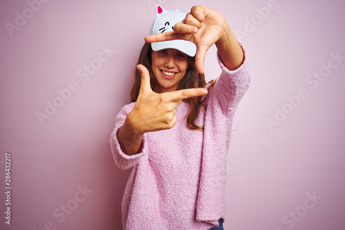 Young beautiful woman wearing funny cat cap standing over pink isolated background smiling making frame with hands and fingers with happy face Wallpaper Mural