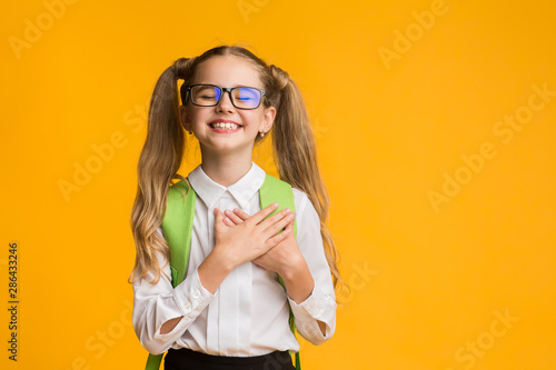 Carta da parati  Cute schoolgirl posing putting hands on heart on yellow background