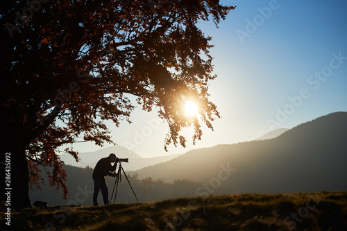 Foto auf Leinwand Schwarz Silhouette of tourist photographer using tripod and professional camera to take picture of mountain panorama at sunset, standing under large tree on foggy mountains landscape and blue sky background.