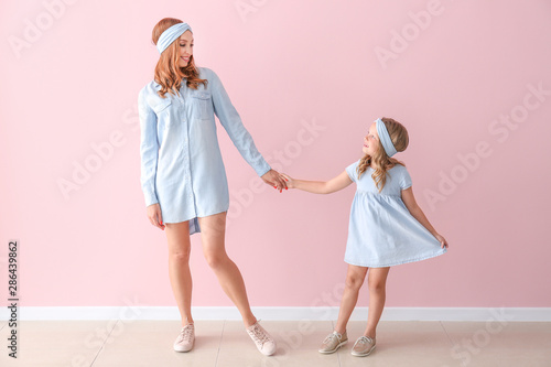 Obraz Beautiful woman and her little daughter near color wall - fototapety do salonu
