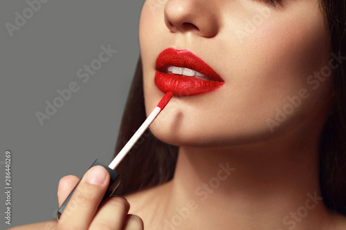 Fotografiet  Beautiful young woman with bright lipstick on grey background, closeup