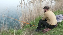 Fisherman Sits And Fishes On The Shore. Man Waiting A Fish With A Fishing Rod.