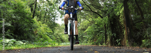 Photo Woman cyclist riding mountain bike on tropical rainforest trail