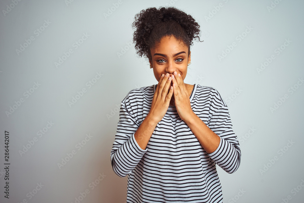 Fototapety, obrazy: African american woman wearing navy striped t-shirt standing over isolated white background laughing and embarrassed giggle covering mouth with hands, gossip and scandal concept