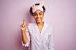 Young african american woman wearing pajama and mask over isolated pink background smiling and confident gesturing with hand doing small size sign with fingers looking and the camera. Measure concept.