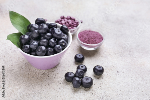 Foto auf Leinwand Natur Acai berries with powder and tablets on light background