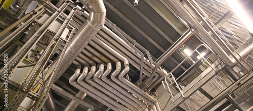 Fototapeta Equipment, cables and piping as found inside of a modern industrial power plant obraz