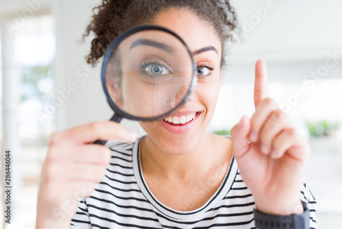 Canvastavla Young african american woman looking through magnifying glass surprised with an