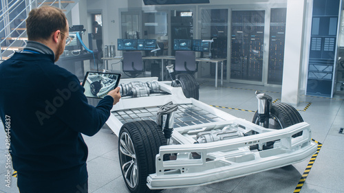 Engineer with Glasses and Beard Scans Electric Car Chassis Prototype with Wheels, Batteries and Engine with an Augmented Reality Software on a Tablet Computer in a High Tech Development Laboratory Canvas Print