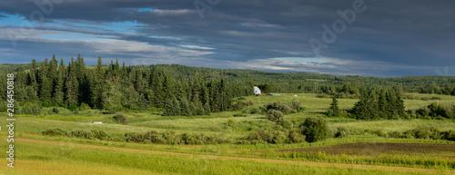 Obraz na plátne paisaje rural en Edson Alberta Canada, con una pequeña casa de campo, en medio del bosque en un día lluvioso de verano con nubes llenas de agua, un cielo azul intenso