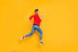 Full body profile side photo of cheerful lady running wearing red striped shirt jacket denim jeans isolated over yellow background