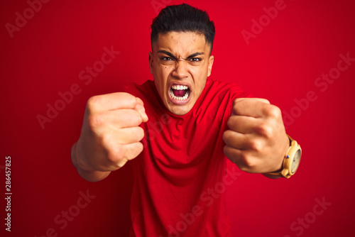Fotografie, Tablou Young brazilian man wearing t-shirt standing over isolated red background angry and mad raising fists frustrated and furious while shouting with anger