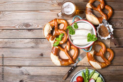Photographie Pretzels, white bavarian sausages and vegetables on wooden background, german tr