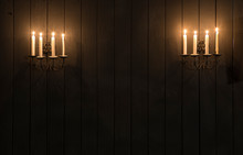 Vintage Wall Candlesticks With Candles On A Black Wooden Wall