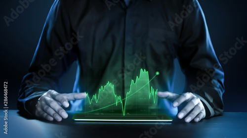 Fototapeta Business man showing profitable stock market holographic technology graphs in modern work background for the future. Company managers in concept planning and managing global marketing and investment. obraz